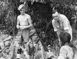 Mr F B K Drake (right), Civilian Liaison Officer-in-Charge of Dyak trackers in Malaya, talks with some of his selected jungle fighters. Photo: Central Office of Information